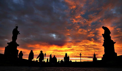 People cross the medieval Charles Bridge as the sun rises in Pra