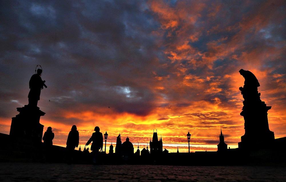 People cross the medieval Charles Bridge as the sun rises in Pra